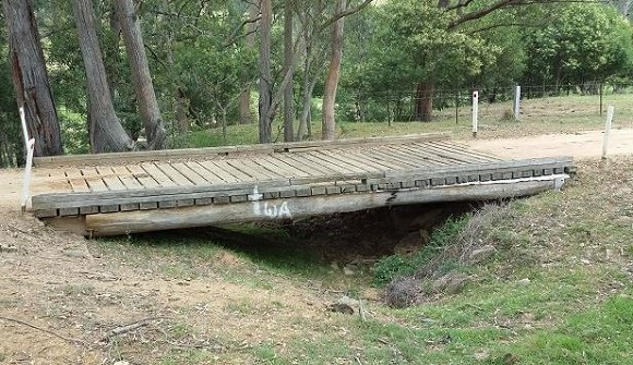 A single span timber bridge crosses a small gully