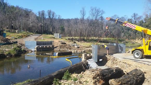 A mobile crane lowers a steel bridge abutment into place.