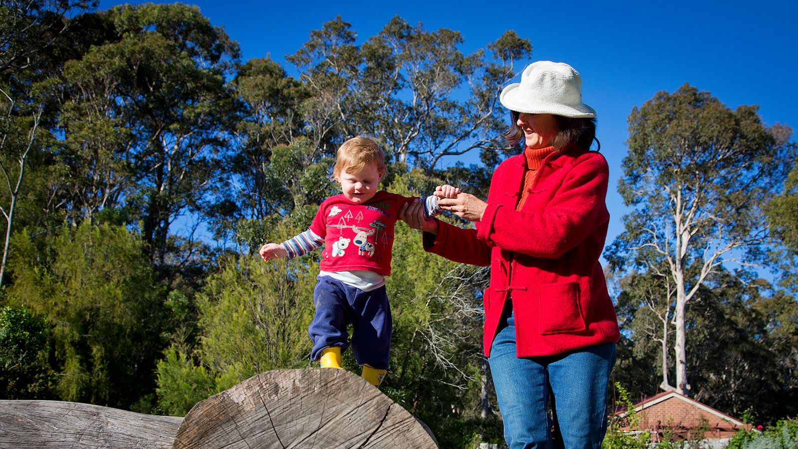 A woman holding the hand of a young child balancing on a large rock. banner image