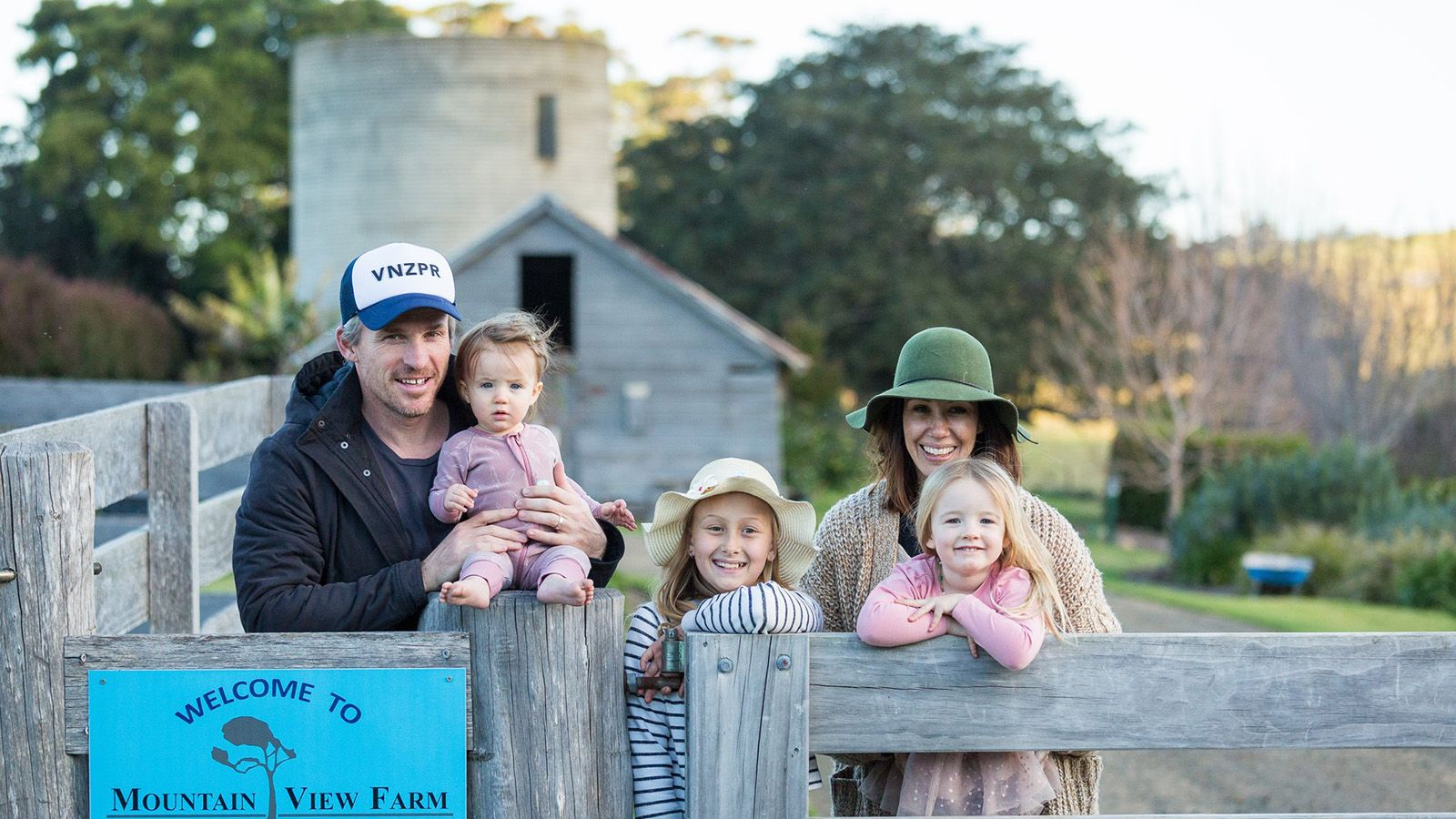A young family of five standing behind a farm style fence banner image