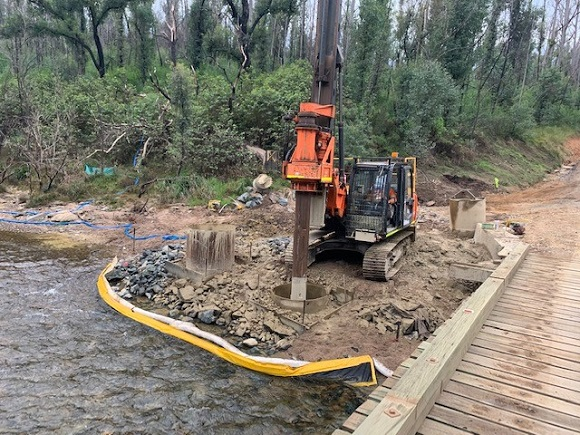 A tracked machine drills vertical piles adjacent to the old timber bridge.