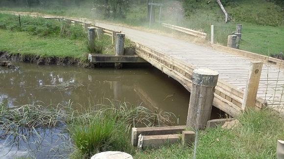 A low single span timber bridge crosses over a creek.