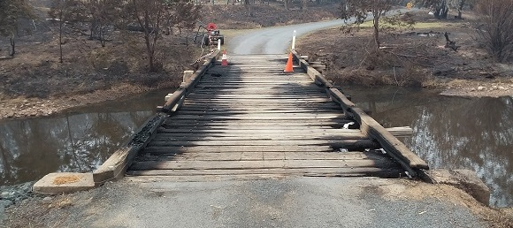 The timber bridge is largely burnt along each side