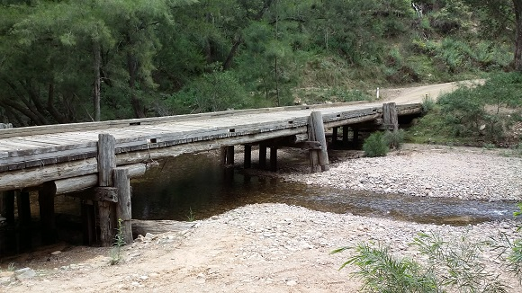 A mulit-span timber bridge passes over a wide riverbed