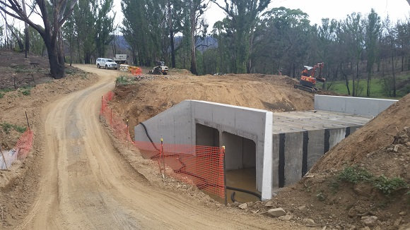 Huge concrete box culverts sit next to the temporary side track