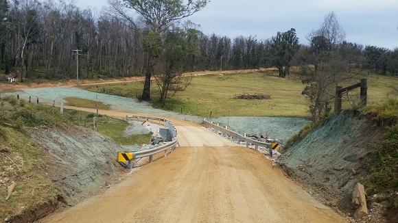 Guardrail aligns a new bridge on a dirt road.