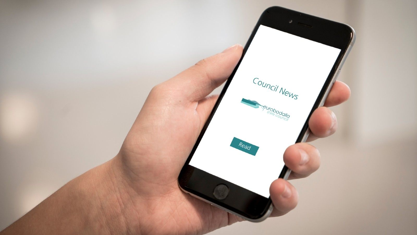 A person's hand holding a mobile phone with 'Council News, read now' displayed on the screen. banner image