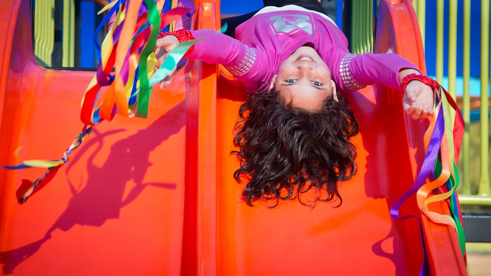 A young girl laying upside down at the top of a playground slide. banner image