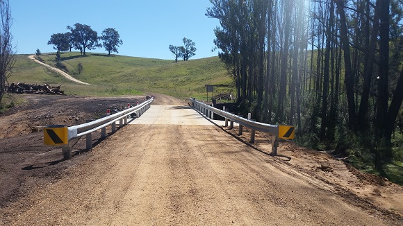 A dirt road leads to a concrete bridge lined with guardrail