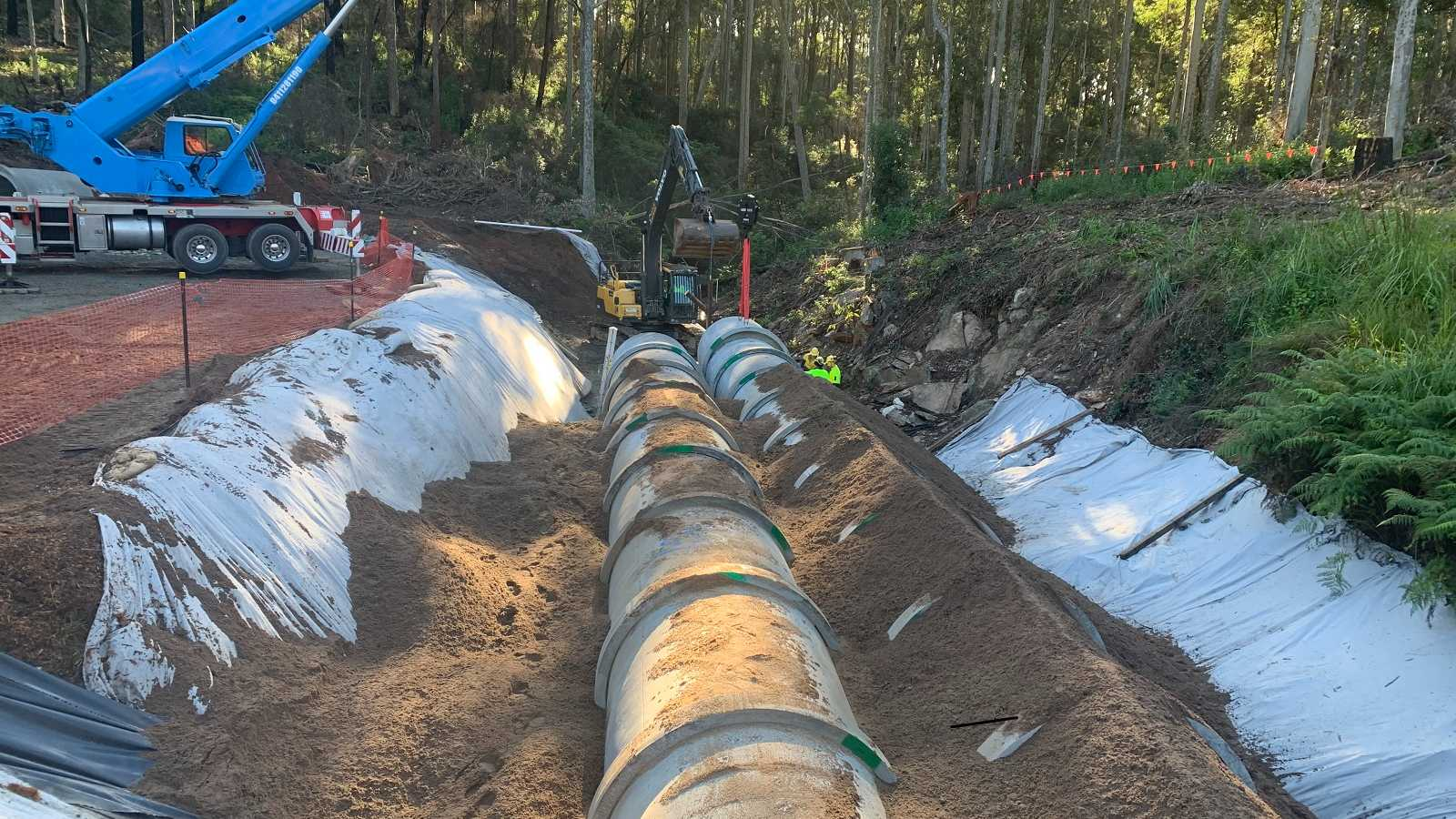 Heavy plant are placing two long concrete culvert extensions in a gully.
