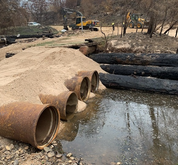 Large pipes and sand lay along the river bed providing temporary access.