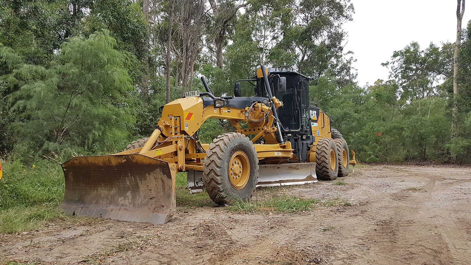 A yellow grader machine parked on a dirt road banner image