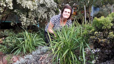 A woman crouches in a lovely native garden.