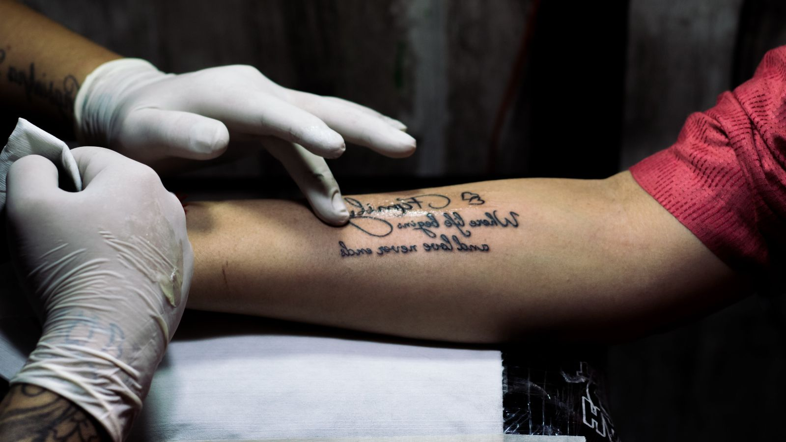 Tattoo artist's hands tattooing person's arm banner image