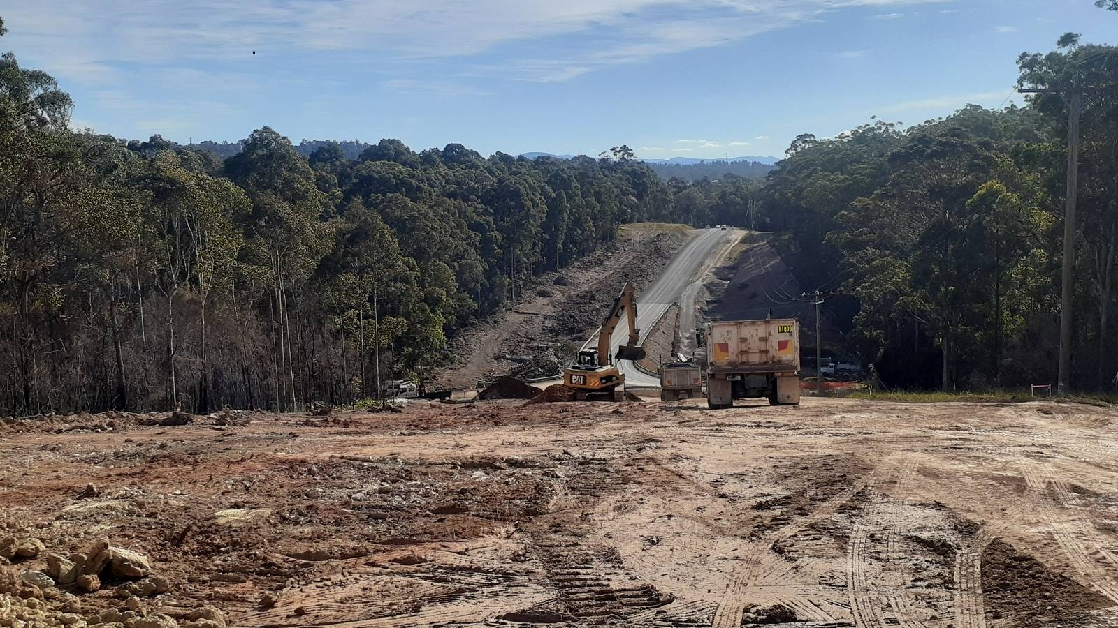 Heavy plant work in a large cleared area surrounded by forest.