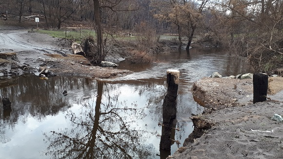 Flood waters wash away the temporary track across the creek