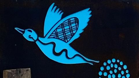 Close up of roadside sign with image of blue duck
