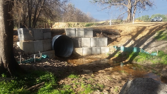 A steel pipe runs under the road supported by large concrete blocks