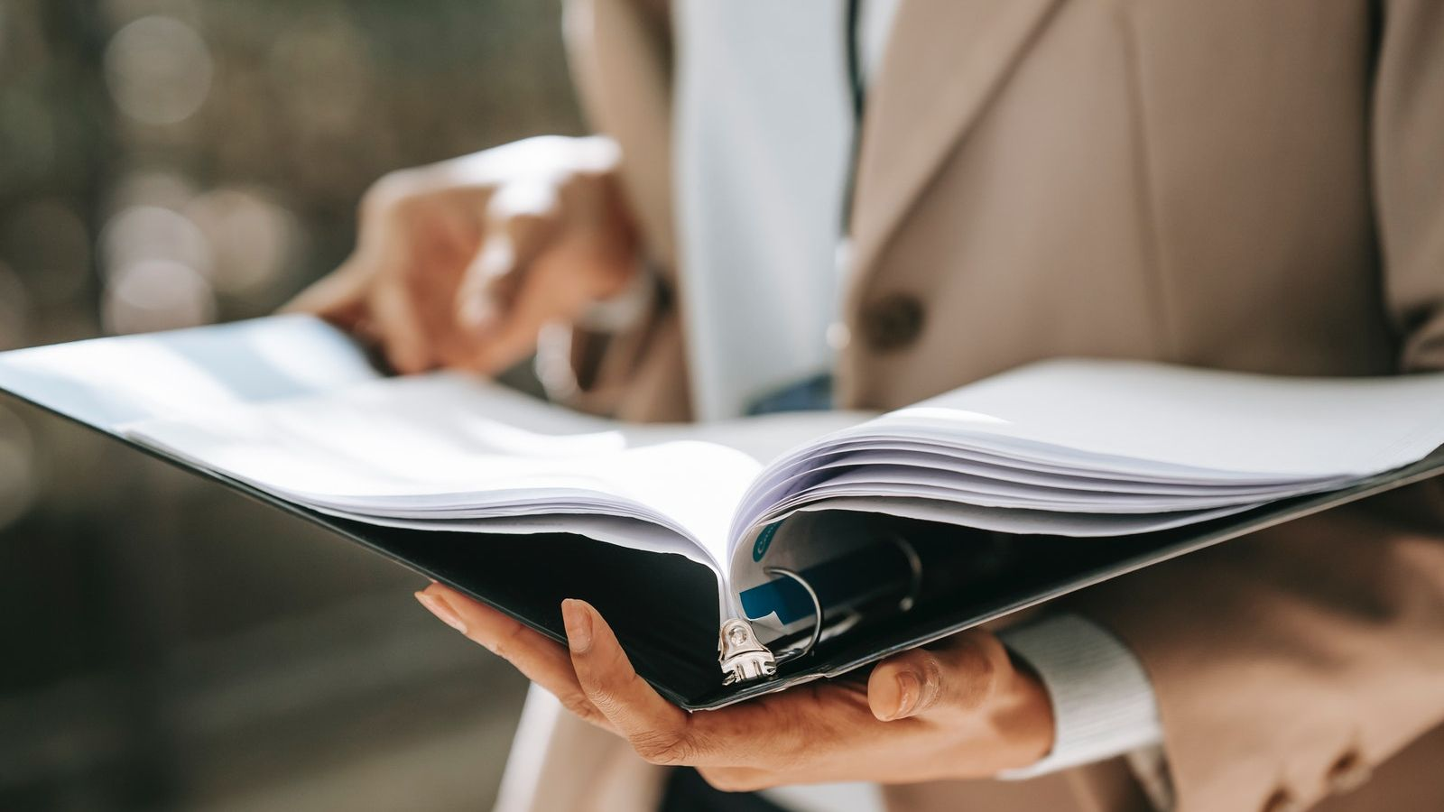 Woman's hands holding a black folder with white pages banner image