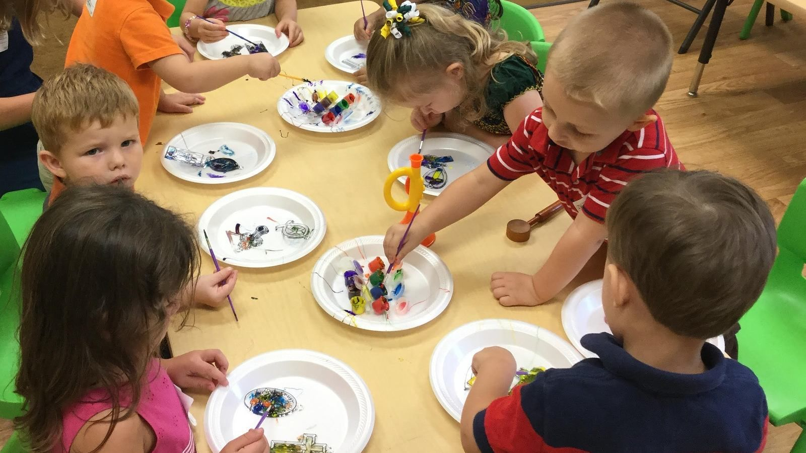 Preschool kids sitting on a table together doing craft banner image