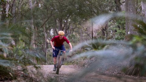 Man in red shirt riding mountain bike on dirt trails