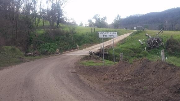 A dirt road with a timber bridge winds through green farmland