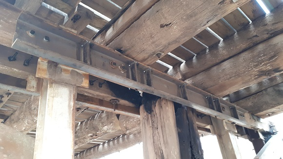 A large steel beam is bolted to the underside of a timber bridge