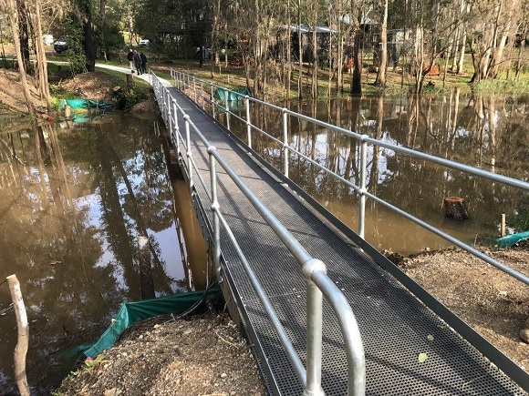 A new steel footbridge crosses a creek