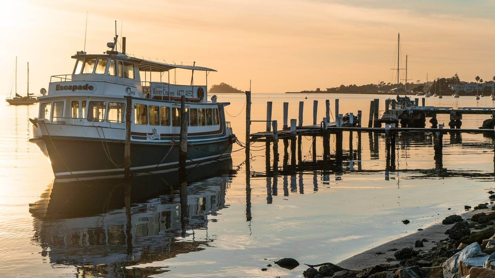 Cruise boat docked at the wharf with sunset in the background banner image