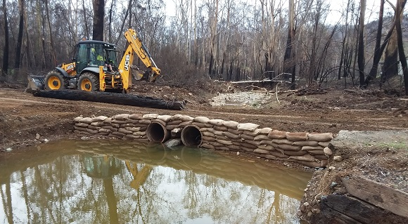 Pipes and sandbags help form a temporary track over muddy waters