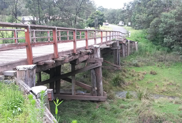 The timber bridge sits high above the creek