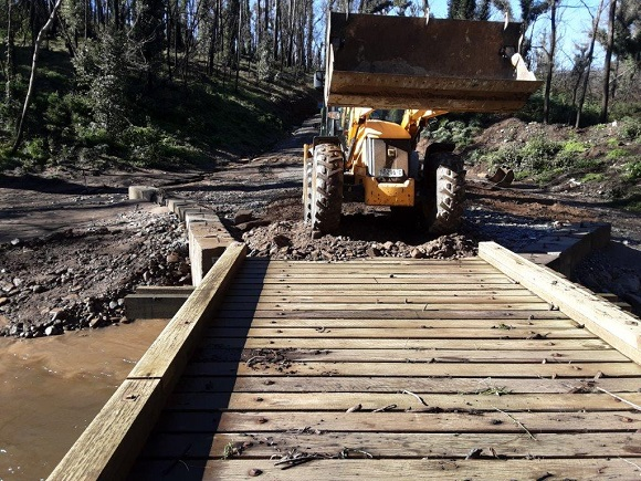 A loader works to restore access across atimber bridge