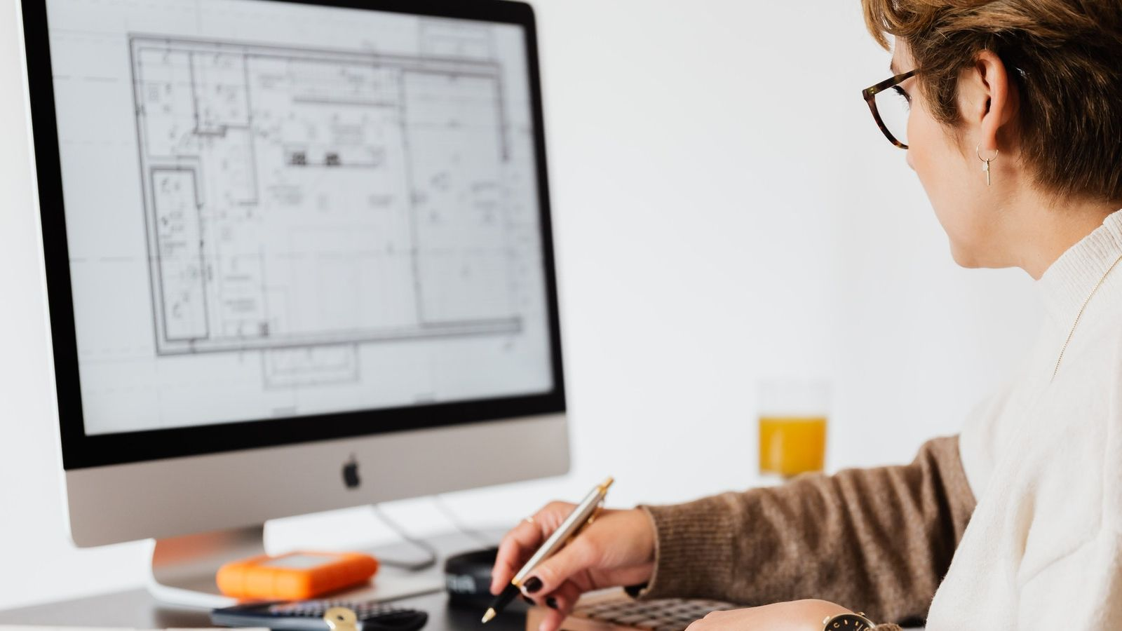 Woman looking at building plans on a computer screen banner image