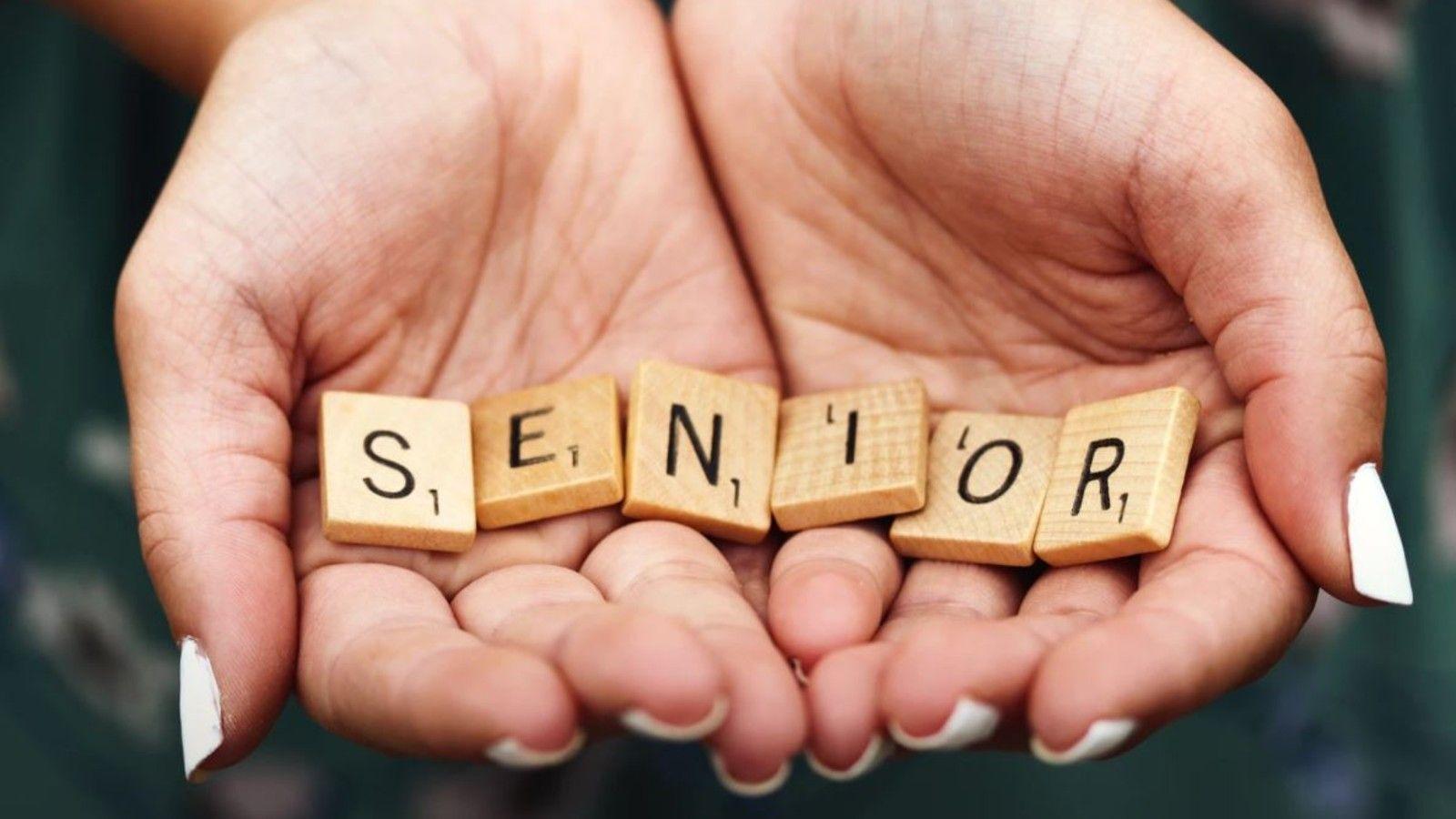 Hands holding scrabble letters spelling senior banner image