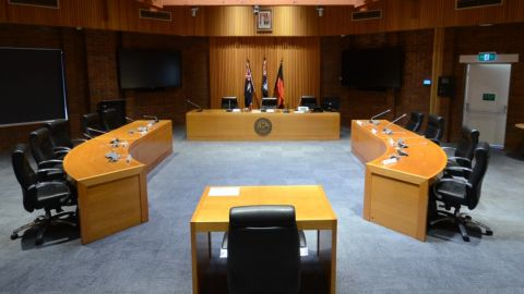 The empty Council Chambers - desks in a circle facing each other with empty seats.