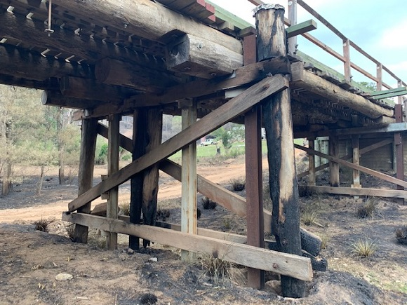 The upright structural timbers of the bridge are burnt