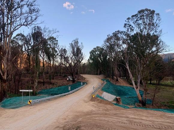 A fresh dirt road runs over a gully