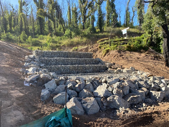 Rows of gabion baskets and rocks are stepped up a steep slope