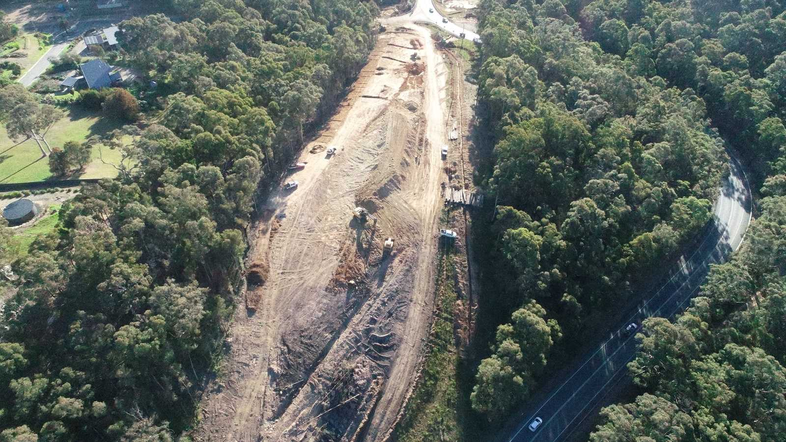 An aerial image shows earthworks cutting a road through a forested area