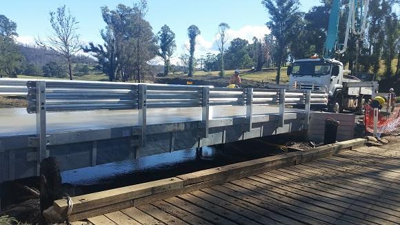 A new aluminium and concrete bridge sits higher than the old bridge