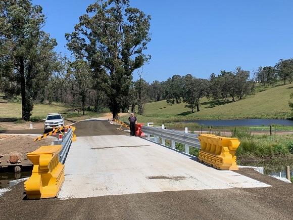 A concrete bridge is lined with guardrail