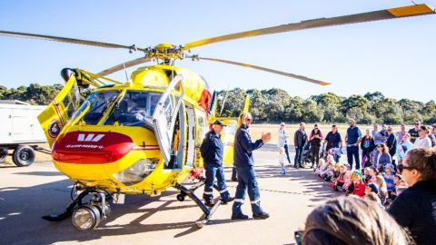 Two rescue team members standing in front of a Westpac helicopter talking to a crowd of people.