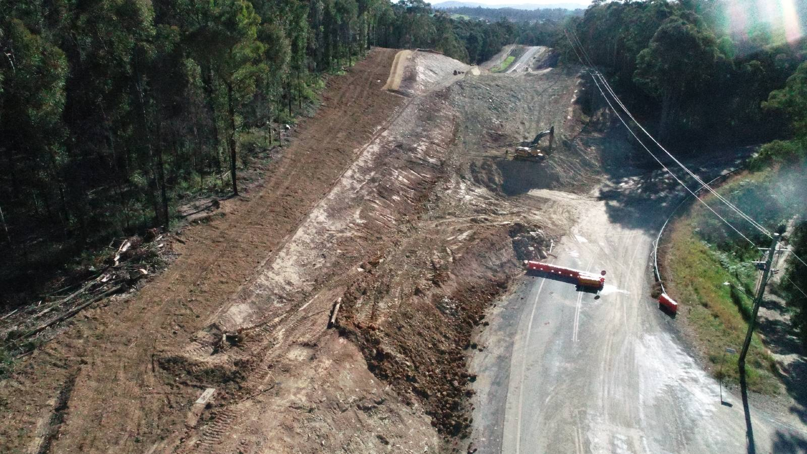 An aerial photo shows major earthworks underway cutting a road through a hill