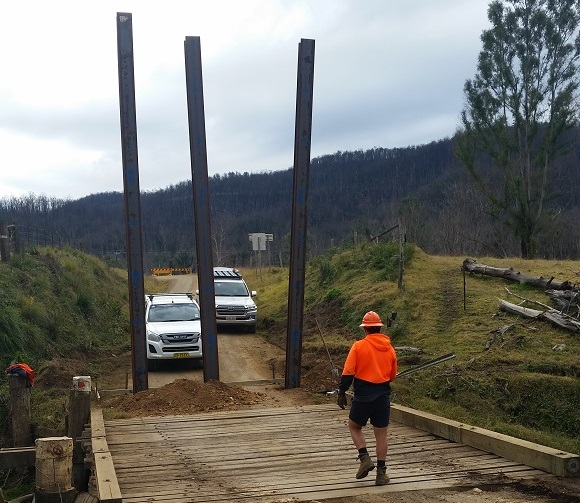 Three steel piles stand tall at the end of the bridge