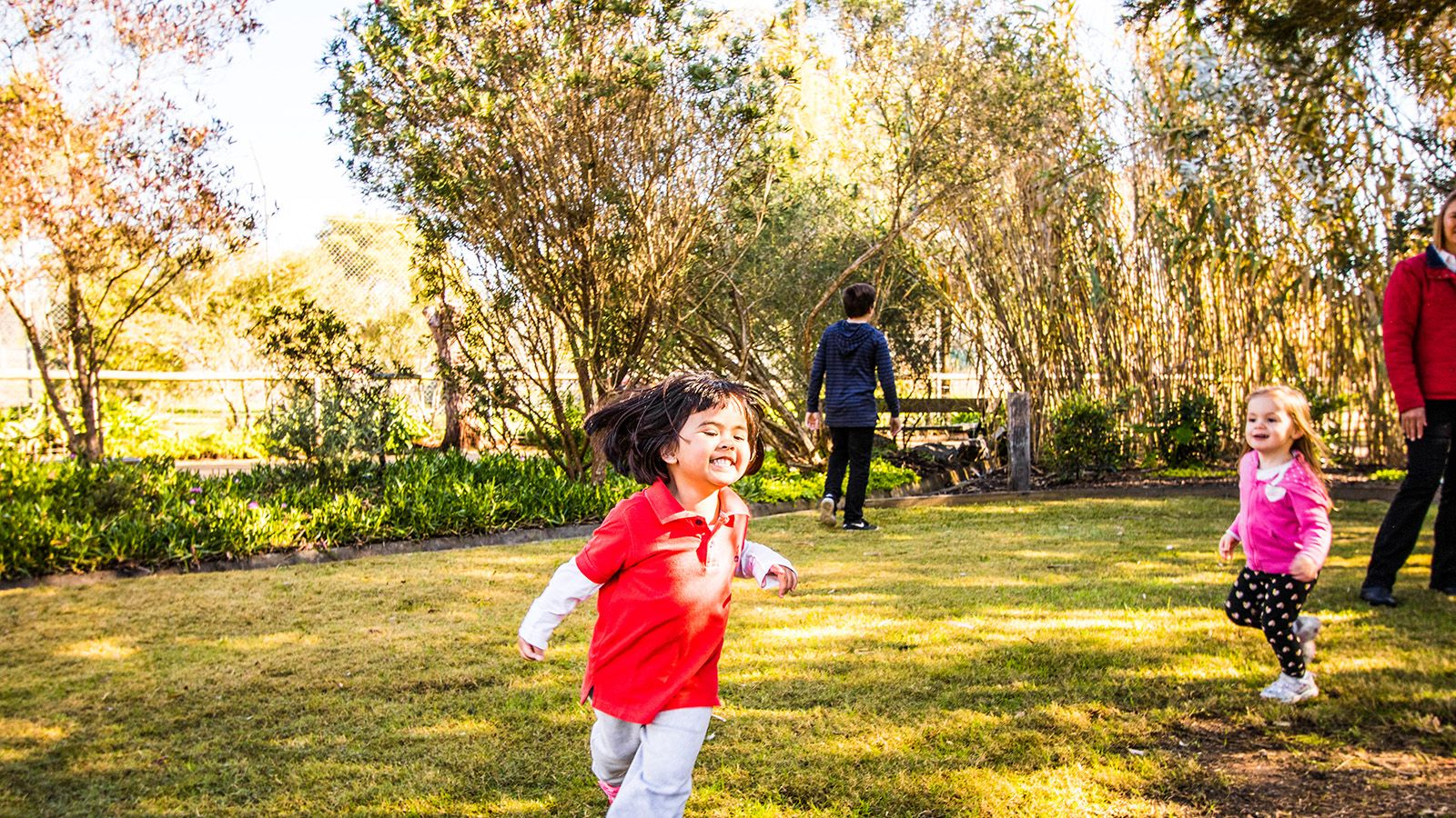 Two young children in bright clothing running outside on the grass banner image