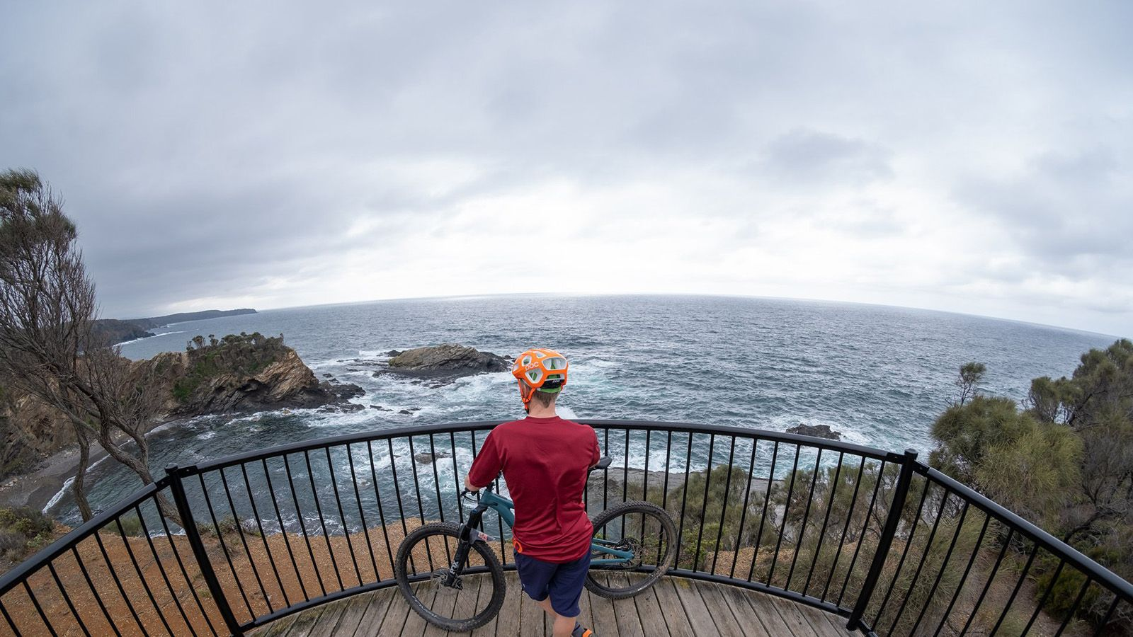A cyclist standing next to his bike looking out over the water at a lookout with a railing banner image