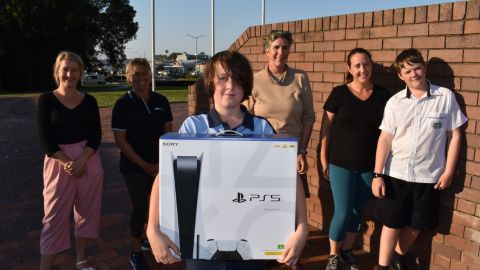 Six people stand in a group, with a boy at the front holding a PS5 box.