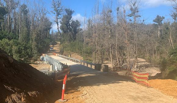 Guardrail lines a concrete bridge on a dirt road.