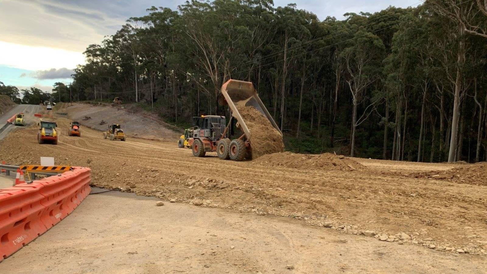 A dump truck tips a load of dirt onto a vast earthworks site