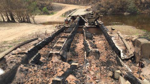 Burnt out bridge across large sandy river bed.